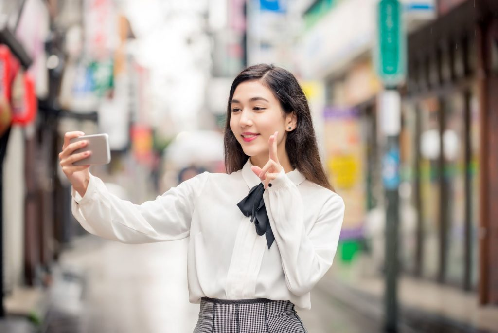 Joven japonesa se toma una foto al aire libre